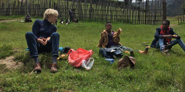 3 Personen sitzen im Gras in Äthipien und unterhalten sich